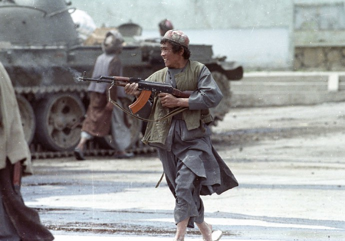 A Dostum mujahideen fighter runs as he fires his AK-47 machine gun