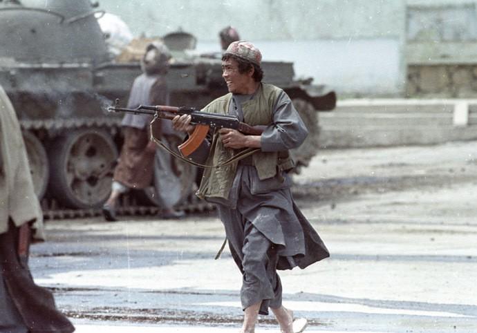 A Dostum mujahideen fighter runs as he fires his AK-47 machine gun