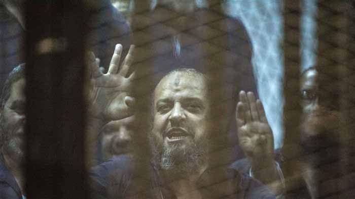 (ภาพ) บุคคลสำคัญระดับสูงของกลุ่มภราดรภาพมุสลิมอียิปต์ Mohamed el-Beltagy ชูสัญลักษณ์มาจากด้านหลังคอกจำเลย เมื่อ 16 พฤษภาคม 2015 ที่โรงเรียนตำรวจในไคโร
