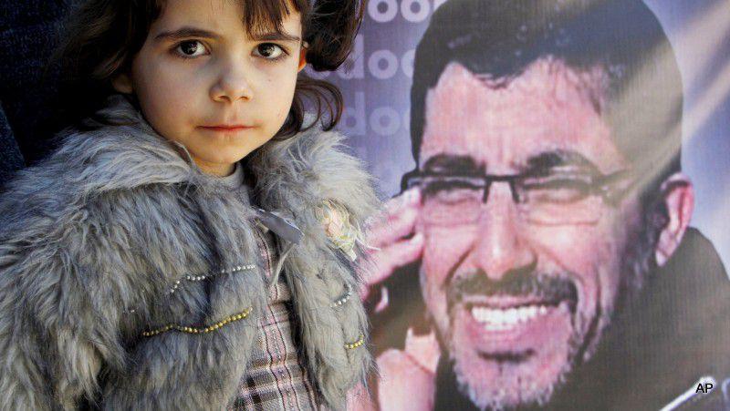 (ภาพ) มาเรีย อบูซีซี หยุดที่หน้ารูปพ่อของเธอ ดิรอร อบูซีซี ระหว่างการชุมนุมแสดงความเป็นน้ำหนึ่งใจเดียวเพื่อเรียกร้องให้ปล่อยตัวเขาจากคุกของอิสราเอล หน้าสำนักงานใหญ่ UNRWA ในกาซ่าซิตี้ เมื่อ 22 มีนาคม 2011 กลุ่มสิทธิมนุษยชนปาเลสไตน์กลุ่มหนึ่งเปิดเผยรายละเอียดใหม่เกี่ยวกับอบูซีซี ที่หายตัวไปจากรถไฟขบวนหนึ่งของยูเครน และปรากฏตัวอีกครั้งในเรือนจำอิสราเอล โดยกล่าวว่า เขาถูกสายลับอิสราเอลพาตัวไปจากตู้นอนของเขา สวมฮู้ดและใส่กุญแจมือ ถูกบังคับขึ้นเครื่องบินและนำตัวไปยังอิสราเอล