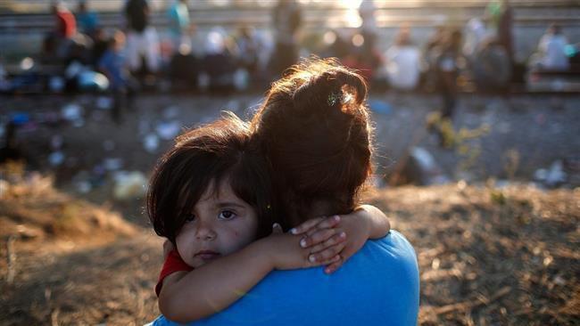 (ภาพ) เด็กหญิงผู้ลี้ภัยตัวน้อยที่แม่อุ้มไว้ใกล้กับทางรถไฟในเมืองไอโดเมนี ประเทศกรีซ เพื่อรอข้าไปยังมาซิโดเนีย เมื่อ 2 กันยายน 2015