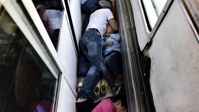 (ภาพ) ผู้ลี้ภัยชาวซีเรียนอนบนพื้นรถไฟที่กำลังพาพวกเขาจากมาซิโดเนียไปยังชายแดนเซอร์เบีย เมื่อ 30 สิงหาคม 2015