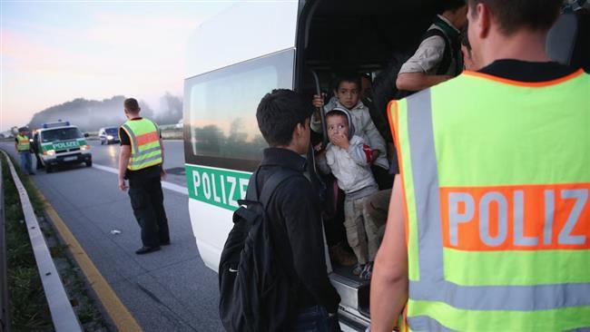 (ภาพ) ตำรวจลำเลียงผู้ลี้ภัยชาวอัฟกันขึ้นรถตู้คันหนึ่ง หลังจากผู้ขอลี้ภัยกลุ่มนี้ได้ข้ามจากออสเตรียเข้ามาในเยอรมนี เมื่อ 30 สิงหาคม 2015