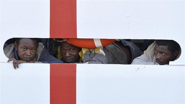 (ภาพ) ผู้ลี้ภัยรอขึ้นฝั่งจากเรือ Diciotti เรือรักษาชายฝั่งของอิตาลี่ ที่ท่าเรือเมสซิน่า ในเมืองซิซิลี ประเทศอิตาลี่ เมื่อ 29 สิงหาคม 2015