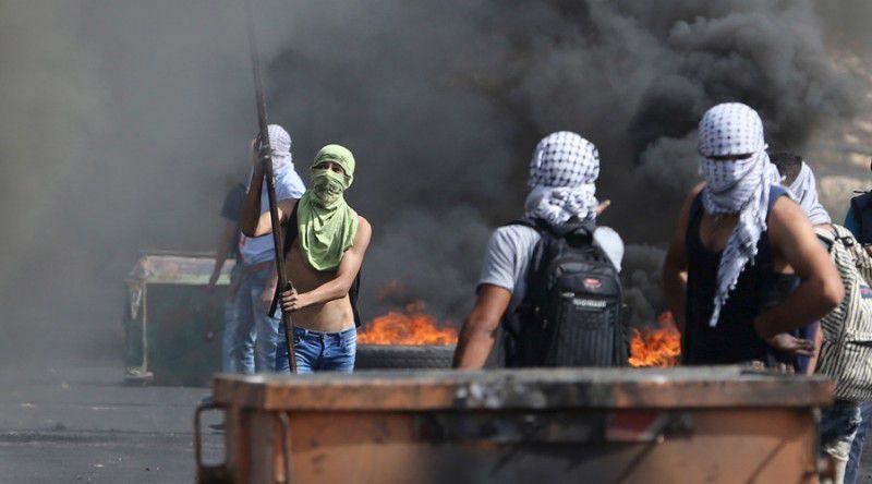 (ภาพ) ผู้ประท้วงชาวปาเลสไตน์ที่ปิดหน้าหาที่กำบังระหว่างการปะทะกับกองทหารอิสราเอลใกล้กับนิคมชาวยิวใน Bet El ใกล้เมืองมารัลลอฮ์ของเวสต์แบงก์ เมื่อ 12 ตุลาคม 2015 © Mohamad Torokman / Reuters