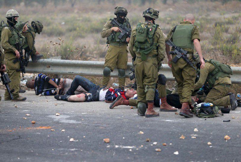 (ภาพ) ทหารอิสราเอลปฏิบัติกับผู้ประท้วงชาวปาเลสไตน์ที่ได้รับบาดเจ็บ ขณะที่คุมตัวพวกเขาไว้ระหว่างการปะทะกันใกล้กับนิคมชาวยิว Bet El ใกล้เมืองรามัลลอฮ์ของเวสต์แบงก์ เมื่อ 7 ตุลาคม 2015 © Mohamad Torokman / Reuters