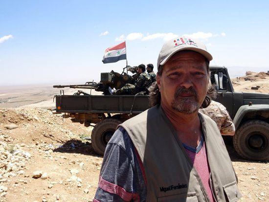 ไมเคิล เฟอร์นันเดซ มาติเนซ ในซีเรีย- ข้างหลังเขาคือ รถ Jeep จากกองทัพซีเรีย การรุกรานที่ได้รับการสนับสนุนทางการเงินจากตะวันตก